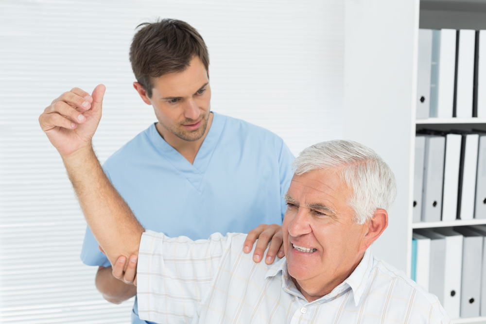 Physician holding the right shoulder of the old man