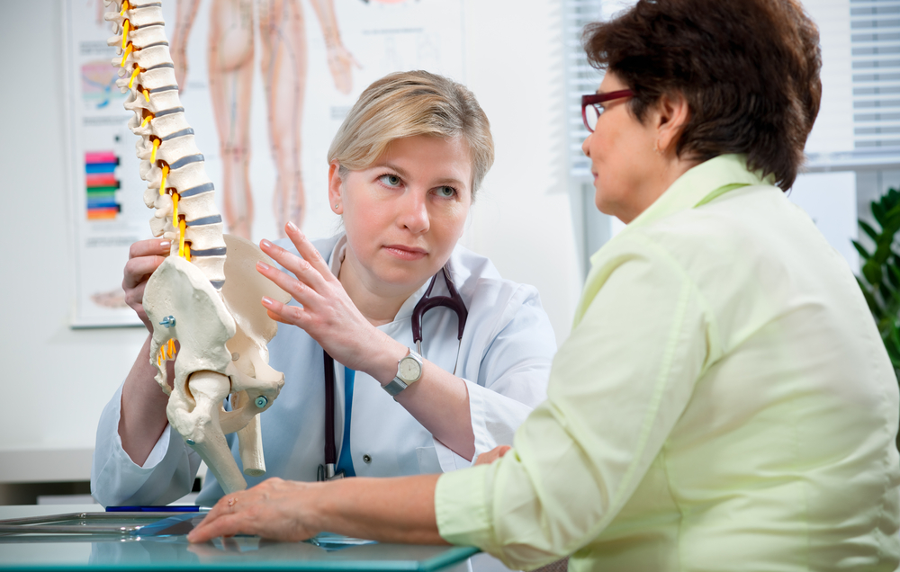 Doctor showing the old lady the structure of the spine
