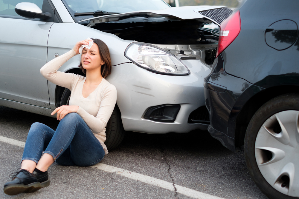 Woman sitting beside the car holding her head